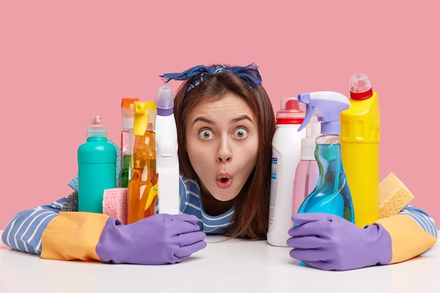 Shocked dark haired lady with widely opened eyes, terrified facial expression, hugs bottles of solvent and spray, stupefied with much housework
