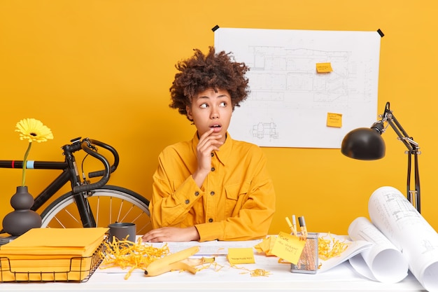 Shocked dark skinned afro american female student works on blueprints dressed in yellow jacket analyzes drawbacks and corrects mistakes in drawings analyzes construction plan looks surprised aside