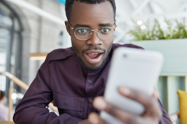 Shocked dark skinned businessman in eyewear, recieves notification on modern smart phone, gets notice to pay bills, has surprised expression.