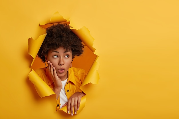 Shocked dark skinned female model looks aside with embarrassement, holds palm on cheekbone, surprised by big discounts, wears fashionable clothes, poses in paper hole, yellow studio background