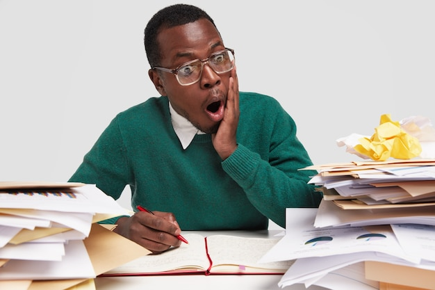 Шокированный темнокожий мужчина с отвисшей челюстью смотрит на таблицу в документе, носит большие прозрачные очки, ошеломлен низким доходом