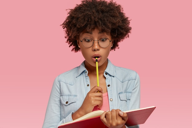 Studente scioccato dalla pelle scura ha lo sguardo stupefatto sul taccuino, porta una matita, sorpreso dalla lista da fare la prossima settimana, ha molti piani e scadenze, indossa occhiali rotondi per una buona visione, ha i capelli ricci