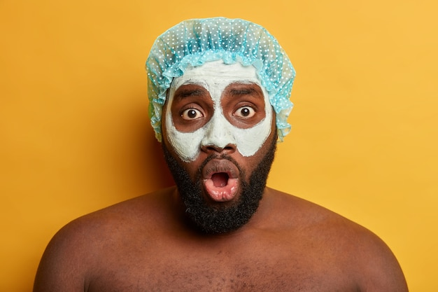 Shocked dark skinned unshaven guy wears clay mask on face, bath cap, stares at camera with eyes popped out, has beauty treatments. skin care concept