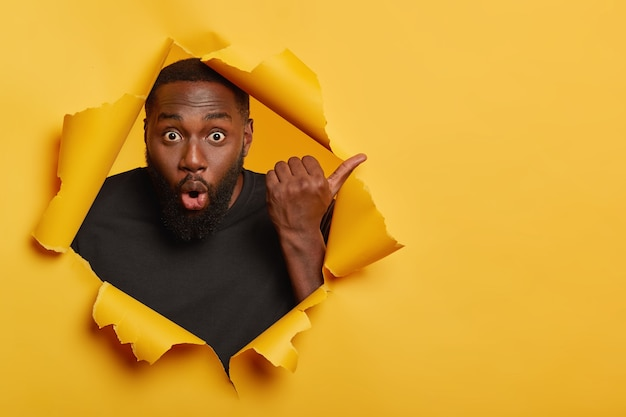 Shocked dark skinned unshaven man points thumb away, feels impressed and stunned, wears black casual t shirt, stands in torn paper hole of yellow background