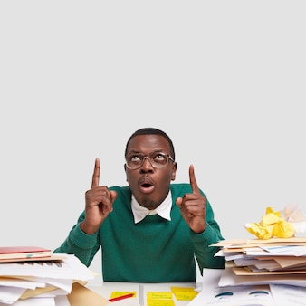 Shocked dark skinned young man points upwards with both index fingers, wears big spectacles, surrounded with pile of papers