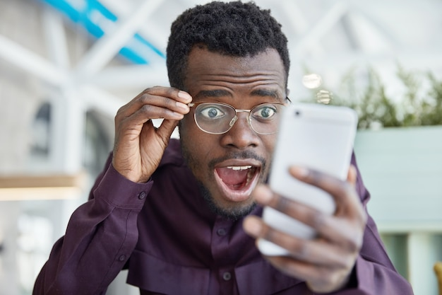 Shocked dark skinned young man stares with bugged eyes, keeps jaw dropped, wears transparent glasses