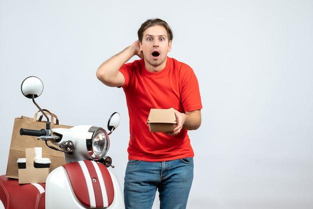 Uomo di consegna scioccato in uniforme rossa che sta vicino al motorino che tiene piccola scatola su fondo bianco