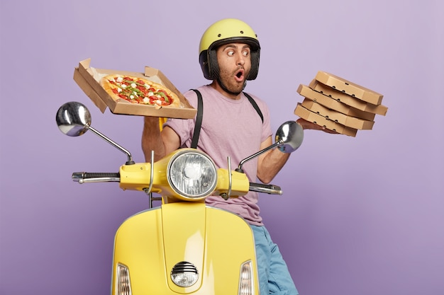 Shocked deliveryman carries stack of delicious italian pizza, wears helmet and casual clothes, drives motorbike, transports fast food for dinner, isolated over purple wall. tasty snack