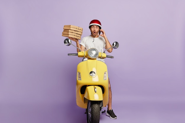 Shocked deliveryman driving scooter while holding pizza boxes