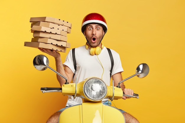 Shocked deliveryman with helmet driving yellow scooter while holding pizza boxes