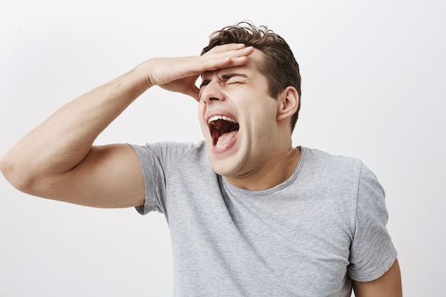 Shocked depressed man dressed casually with appealing appearace screaming, shouting in despair to recieve bad news from relatives. emotional young man gesturing, hiding face behind his hand