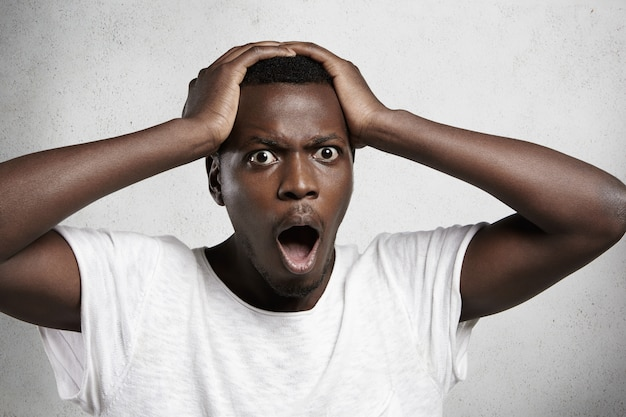 Shocked and desperate dark-skinned man wearing white t-shirt, holding hands on head, looking and screaming with scared expression and mouth wide open because of some terrible mistake