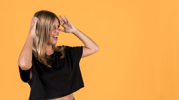 Shocked disable woman standing against bright yellow backdrop