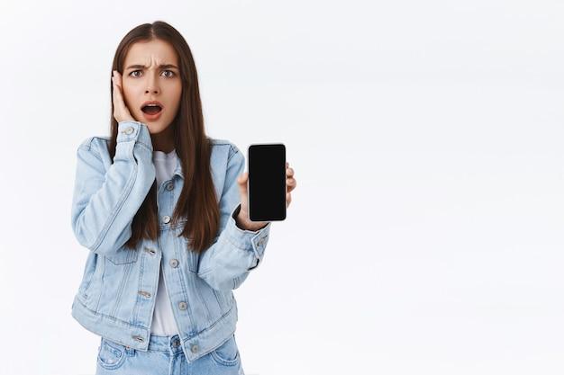 Scioccato e deluso frustrato giovane donna in giacca di jeans, tenendo lo smartphone che mostra qualcosa di inquietante e sconvolgente sul display mobile, accigliato rabbrividire infastidito, tocco guancia
