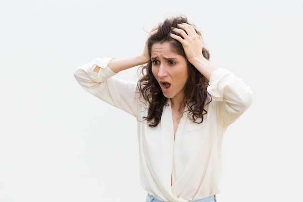 Shocked disappointed woman gasping, holding head