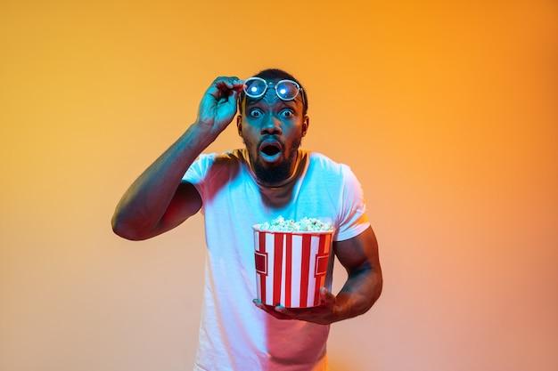 Шокирован, недоверие. современный портрет афро-американского человека на градиентном оранжевом фоне студии в неоновом свете. красивая афро модель. понятие эмоций, кино, мимики, продаж, рекламы.