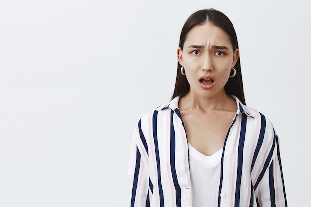 Scioccato scontento attraente giovane donna in camicetta a righe con bellezza naturale, accigliato e ansimante dalla delusione, esprimendo empatia al povero amico, in posa su un muro grigio