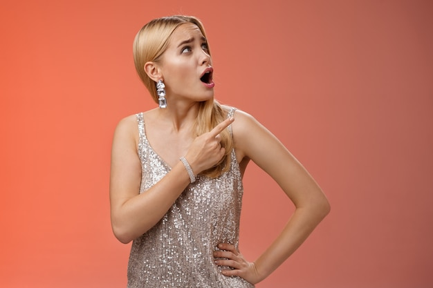 Shocked displeased bothered arrogant blond glamour woman in silver glittering dress turning upper right corner pointing complaining strange noise come upstairs, standing questioned red background.