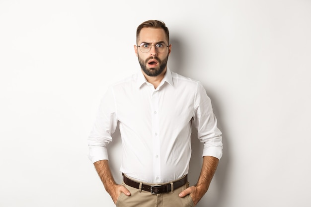 Shocked and displeased businessman in glasses, gasping and looking upset at camera, standing over white background. copy space