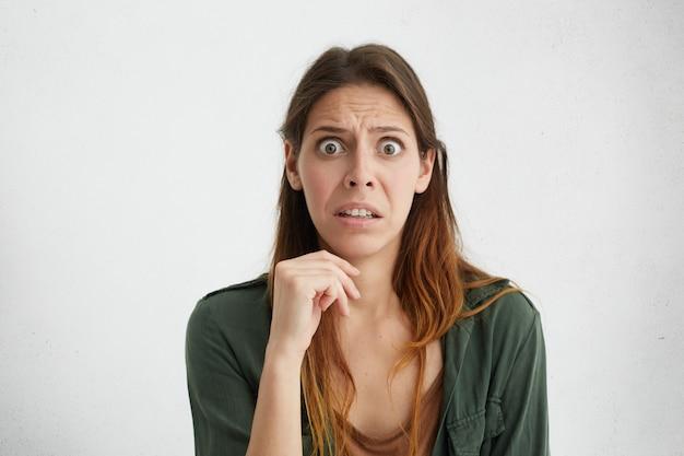Donna scioccata insoddisfatta con i capelli lunghi e grandi occhi scuri che indossano abiti casual tenendo la mano sul mento sorpresa di sentire le notizie.