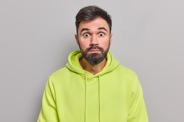 Shocked distressed bearded man stares bugged eyes at camera cannot believe his eyes