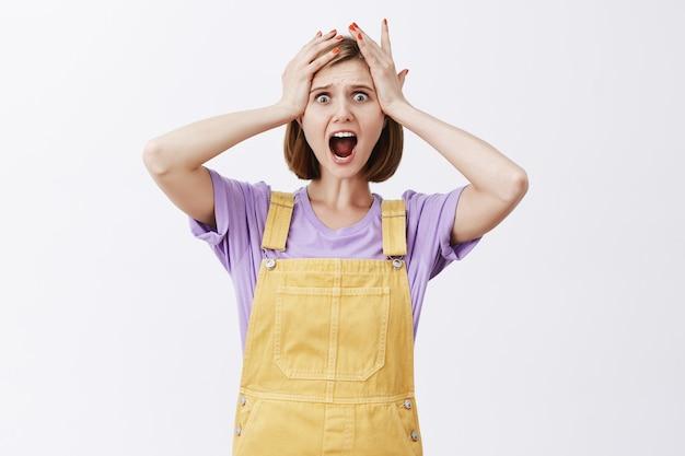 Giovane donna scioccata e angosciata che affronta il disastro, con aria inorridita