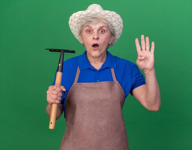 Shocked elderly female gardener wearing gardening hat holding rake and gesturing four with fingers on green
