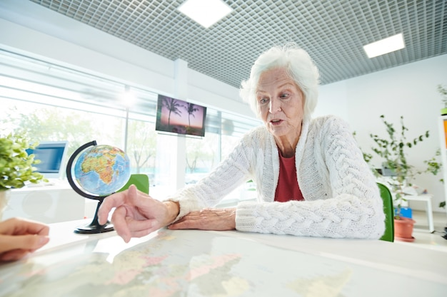Shocked elderly lady pointing at map while talking to trip agent