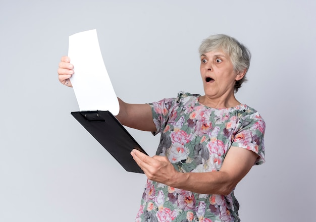 ショックを受けた年配の女性は、白い壁に隔離されたクリップボードを保持し、見ています