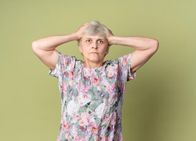 La donna anziana scioccata tiene la testa isolata sulla parete verde oliva