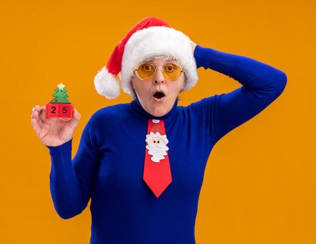 サンタの帽子とサンタのネクタイとサングラスでショックを受けた年配の女性は、クリスマスツリーの飾りを保持し、コピースペースでオレンジ色の背景に分離された頭に手を置きます。