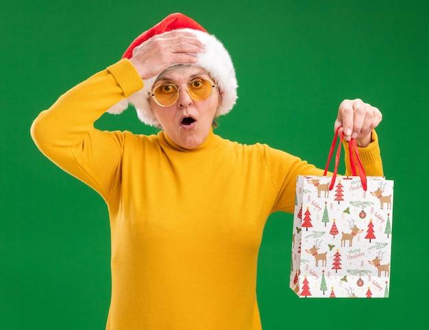 サンタの帽子とサングラスでショックを受けた年配の女性は額に手を置き、紙のギフトバッグを保持します。