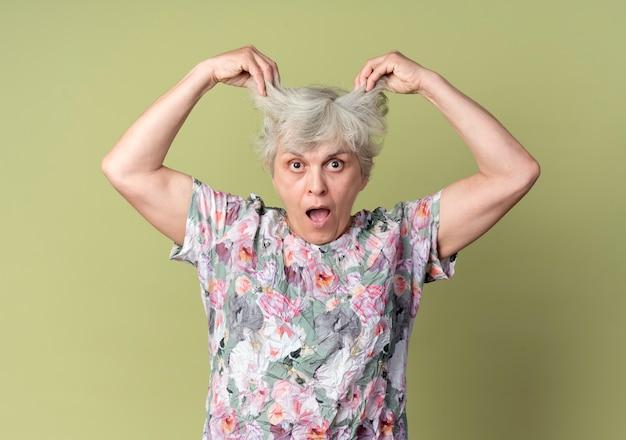 ショックを受けた年配の女性がオリーブグリーンの壁に分離された髪を持ち上げる