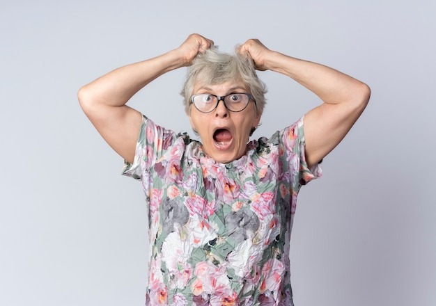 Shocked elderly woman in optical glasses holds and lifts hair looking isolated on white wall