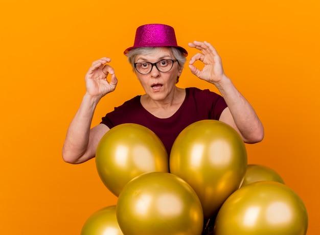 La donna anziana scioccata in vetri ottici che indossa il cappello del partito sta con i palloni dell'elio che gestiscono il segno giusto della mano con due mani isolate sulla parete arancione
