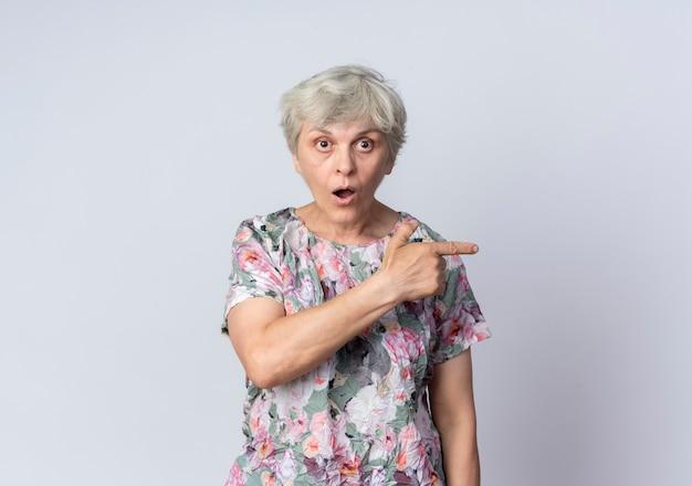 La donna anziana scioccata indica al lato che guarda in avanti isolato sulla parete bianca