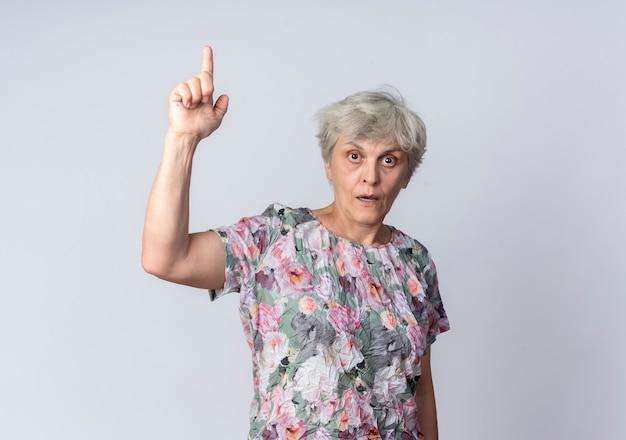 La donna anziana scioccata indica isolato sulla parete bianca