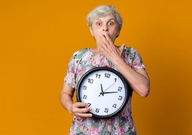 La donna anziana scioccata mette la mano sulla bocca che tiene l'orologio isolato sulla parete arancione