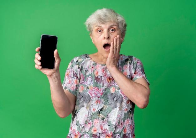 Шокированная пожилая женщина кладет руку на лицо, держа телефон на зеленой стене