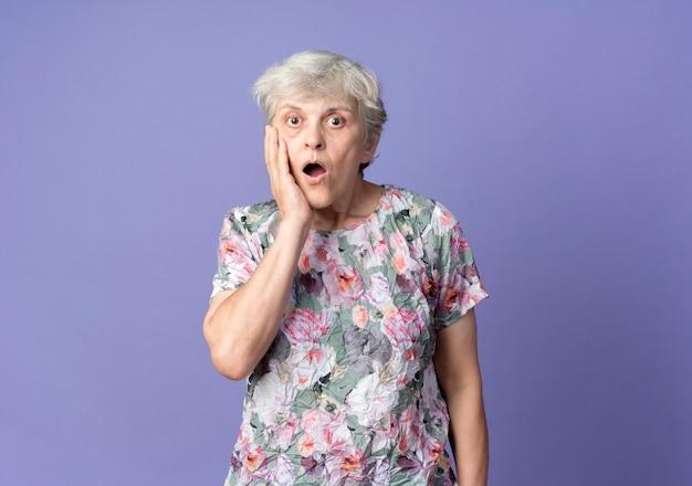 Шокированная пожилая женщина кладет руку на лицо, изолированное на фиолетовой стене