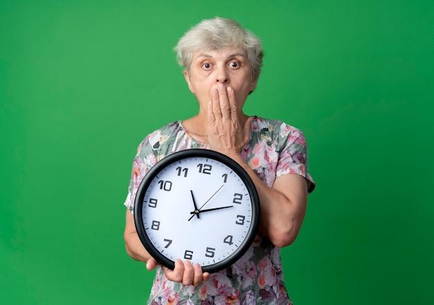 충격 된 노인 여성이 녹색 벽에 고립 된 시계를 들고 입에 손을 넣습니다.