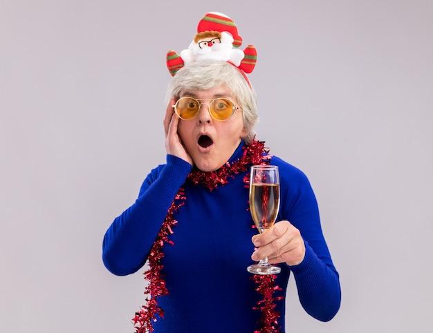 La donna anziana scioccata in occhiali da sole con la fascia della santa e la ghirlanda intorno al collo mette la mano sul fronte e tiene il bicchiere di champagne