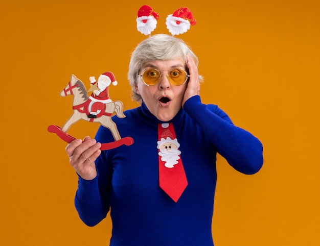 Shocked elderly woman in sun glasses with santa headband and santa tie holding santa on rocking horse decoration and putting hand on face isolated on orange background with copy space