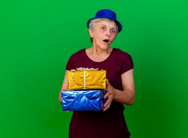 La donna anziana scioccata che indossa il cappello del partito tiene le scatole regalo sul verde