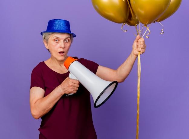 パーティーハットをかぶってショックを受けた年配の女性は、コピースペースで紫色の壁に隔離されたヘリウム気球とスピーカーを保持