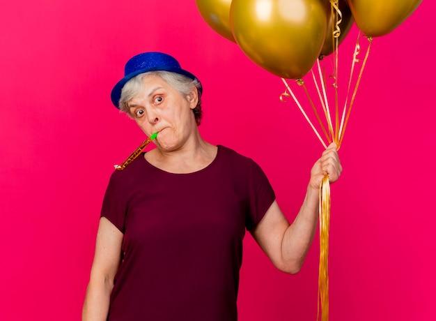 파티 모자를 쓰고 충격을받은 노인 여성이 핑크색에 휘파람을 불고 헬륨 풍선을 보유하고 있습니다.