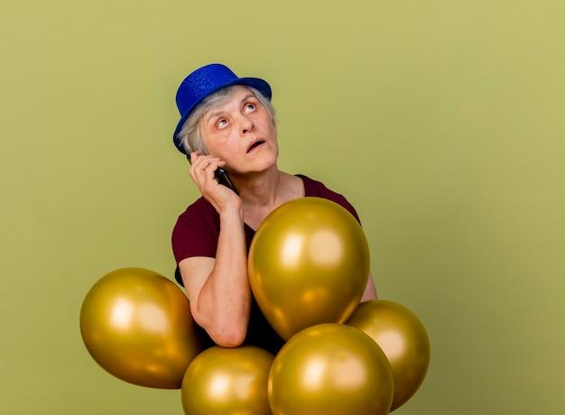パーティーハットをかぶってショックを受けた年配の女性は、オリーブグリーンの壁に隔離された見上げる電話で話しているヘリウム気球を保持します。