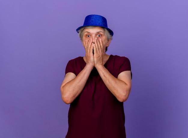 La donna anziana scioccata che indossa il cappello del partito mette le mani sulla bocca isolata sulla parete viola con lo spazio della copia