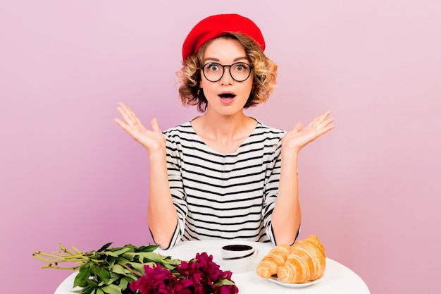 フランスの服のスタイルでショックを受けたエレガントな女性は、広い目の表情で見えます。