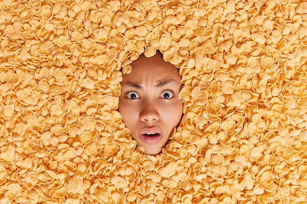 Shocked embarassed woman stares with indignant expression drowned in dry cornflakes has balanced nutrition and dietary ration